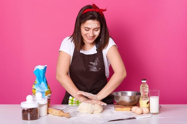 Lo studio ha sparato della pasta d'impastamento della ragazza adorabile con le sue mani al tavolo da cucina Foto Gratuite