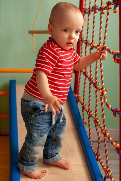 Lo sviluppo fisico del bambino. sport per bambini. palestra per bambini a casa. esercizio sul simulatore. bambino sano, stile di vita sano Foto Premium