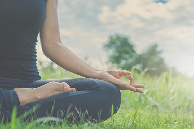 Lo yoga della donna si distende sulla natura. Foto Premium