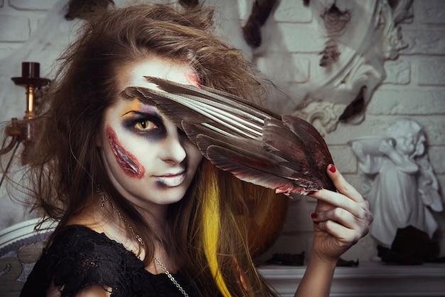 Lo zombie della strega della ragazza mangia l'uccello prima di halloween. la strega si sta preparando per le notti di festa dei morti Foto Premium
