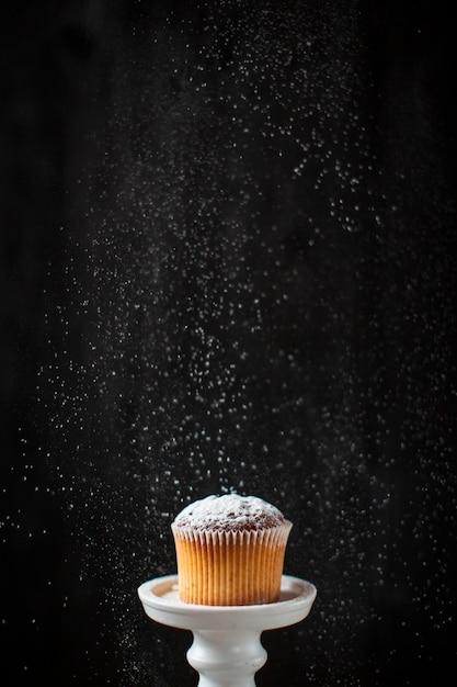 Lo zucchero a velo di vista frontale ha versato sopra il muffin Foto Gratuite