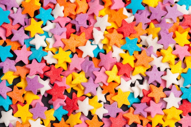 Lo zucchero candito a forma di stella colorato spruzza come fondo Foto Premium