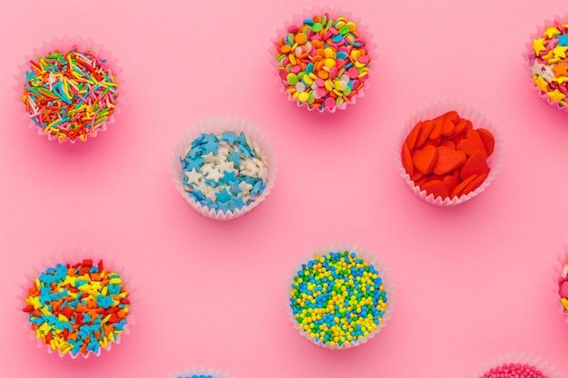 Lo zucchero spruzza, decorazione per torta e gelato e biscotti su sfondo rosa Foto Premium