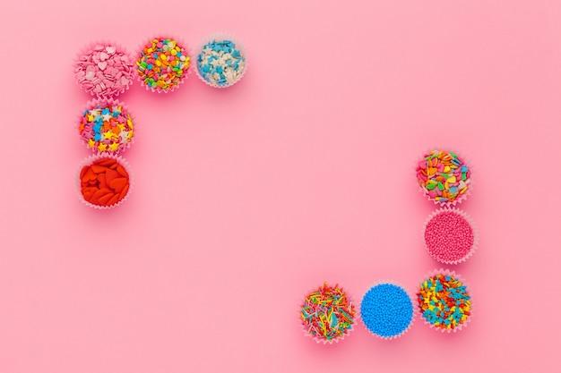 Lo zucchero spruzza, decorazione per torta e gelato e biscotti sul rosa Foto Premium