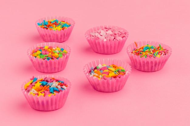 Lo zucchero spruzza il cibo su cartone rosa Foto Premium