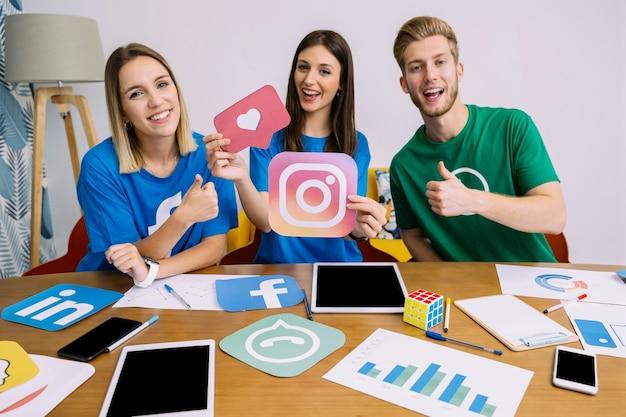 Logo della snapchat della tenuta della donna con i suoi amici che mostrano il segno del thumbup Foto Gratuite