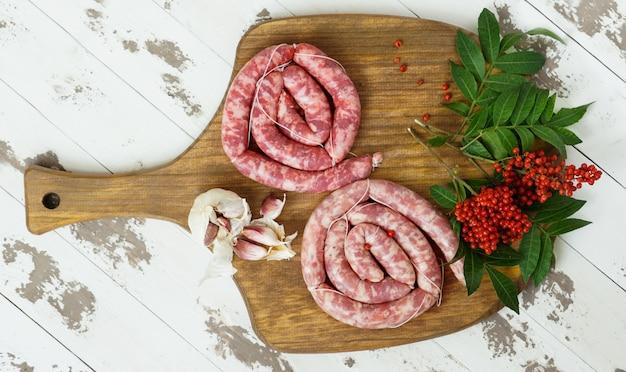 Longaniza spagnola, salsicce di manzo fatte in casa con pepe rosa sul tagliere Foto Premium