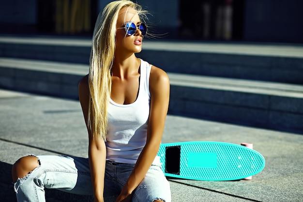 Look di alta moda look.glamor elegante sexy bella giovane modella bionda ragazza in abiti casual casual luminoso estate con skateboard seduto in strada Foto Gratuite