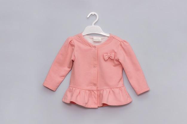 Look in stile ragazza. giacca elegante color rosa pastello sul gancio. concetto dei vestiti di modo dei bambini femminili Foto Premium