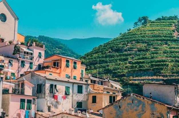 Lotto delle costruzioni vicino alle montagne coperte di erba verde sotto il cielo nuvoloso Foto Gratuite