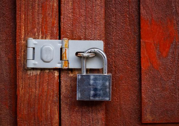 Lucchetto bloccato con la catena al fondo di legno rosso della porta, annata Foto Premium