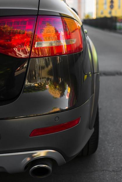 Luce posteriore elegante sulla nuova automobile nera sul percorso Foto Gratuite