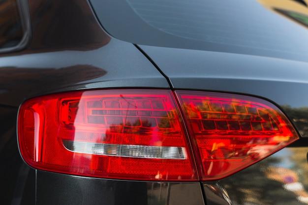 Luce posteriore elegante sulla nuova automobile nera Foto Gratuite