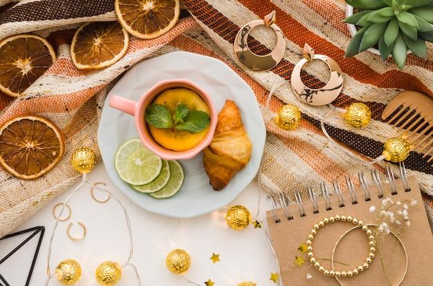 Luci dorate decorative con accessori femminili e tazza di tè sul contesto bianco Foto Gratuite