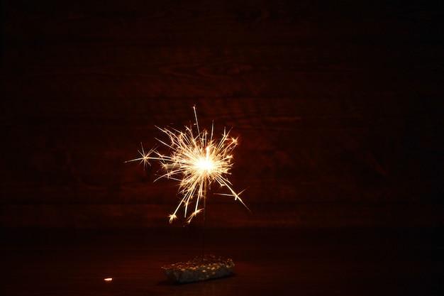 Luci natalizie del bengala al buio. sparkler in fiamme, capodanno. Foto Premium