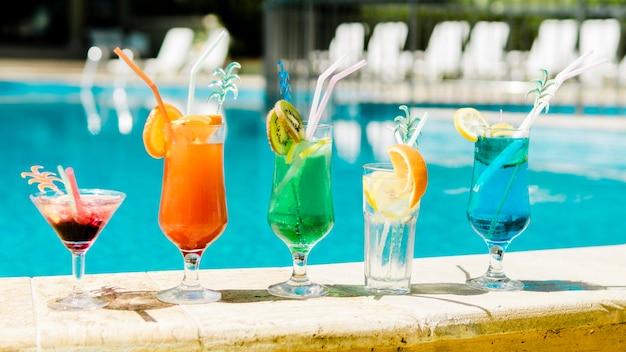 Luminosi cocktail estivi vicino alla piscina Foto Gratuite