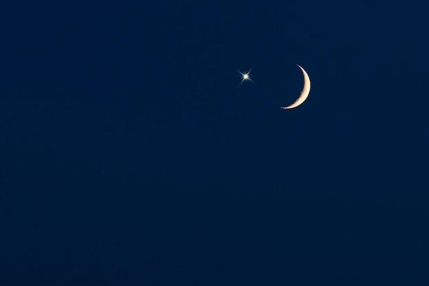 Luna crescente con stella sul cielo blu scuro, immagine per lo sfondo di ramadan o ramazan Foto Premium
