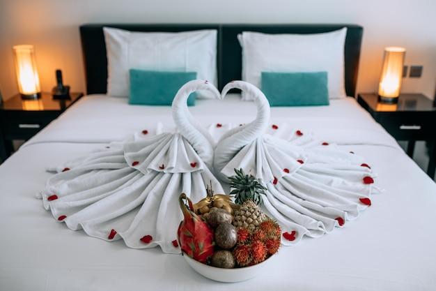 Luna di miele: due bellissimi cigni fatti di asciugamani, situati su un letto bianco con torte di rose, con un grande piatto di frutti esotici. nozze . Foto Premium