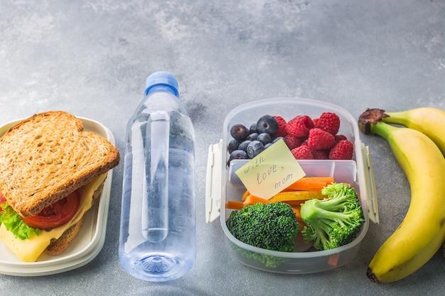 Lunchbox con la bottiglia di broccoli delle carote delle bacche del panino di acqua su gray Foto Premium