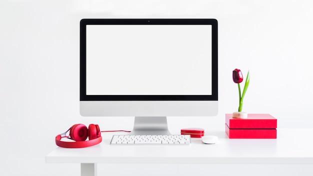 Luogo di lavoro con tastiera vicino a monitor, mouse del computer, fiore ornamento e cuffie Foto Gratuite