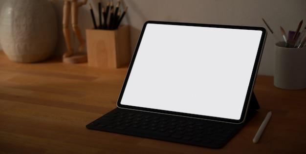 Luogo di lavoro di design con tavoletta digitale schermo vuoto e forniture per ufficio Foto Premium