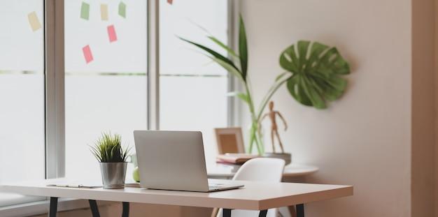 Luogo di lavoro minimal graphic designer con computer portatile aperto Foto Premium