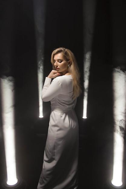 Lussuosa dimensione bionda più con i capelli lunghi bianchi in posa in un lungo abito bianco su un palcoscenico buio nel fumo con la luce. Foto Premium