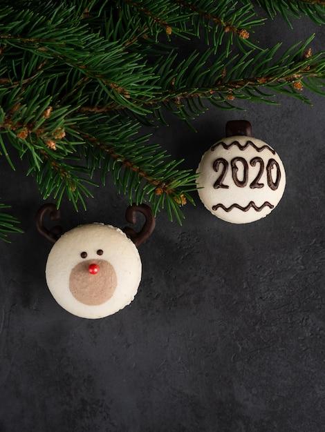 Macaron naso rosso renna e macaron con numero 2020 con abete brances su sfondo nero scuro. carta di natale e capodanno Foto Premium