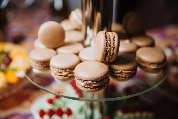 Macarons al cioccolato su uno scivolo di vetro per dessert Foto Premium