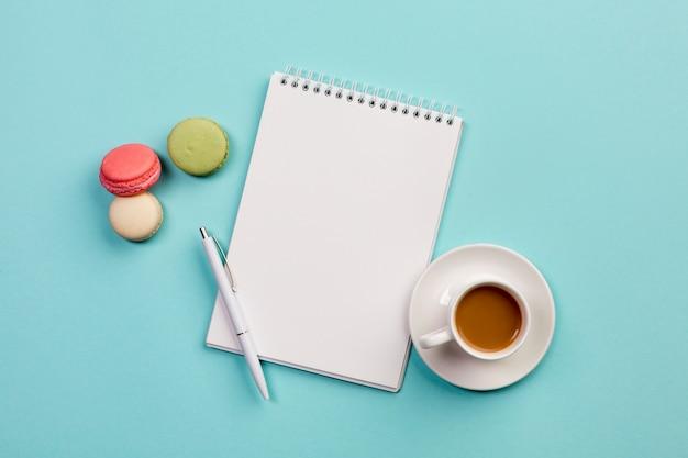 Maccheroni con il blocco note a spirale, la penna e la tazza di caffè su fondo blu Foto Gratuite