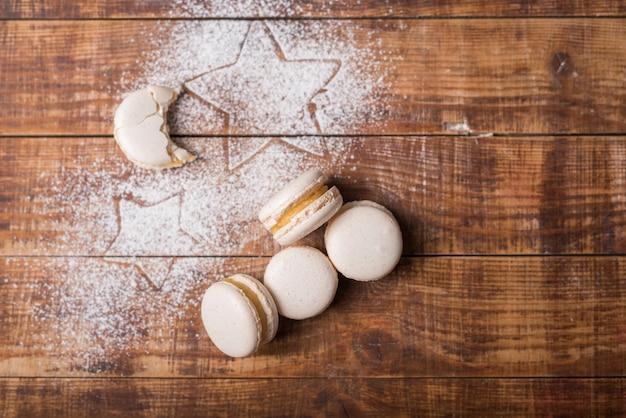 Maccheroni di forma di luna mangiati a forma di stella sulla polvere di zucchero sopra la superficie di legno Foto Gratuite