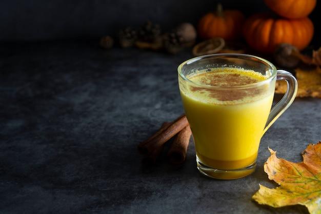 Macchiato di latte speziato di zucca su un legno scuro Foto Premium