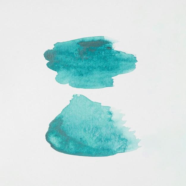 Macchie astratte acquamarina di vernici su carta bianca Foto Gratuite