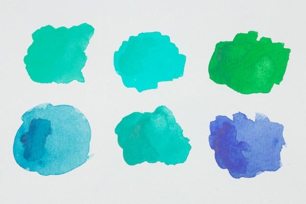 Macchie di verde, blu e acquamarina di vernici su carta bianca Foto Gratuite