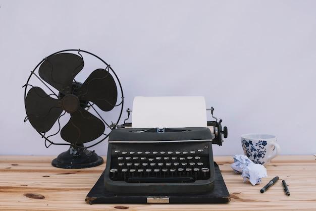 Macchina da scrivere vicino a ventaglio e tazza Foto Gratuite