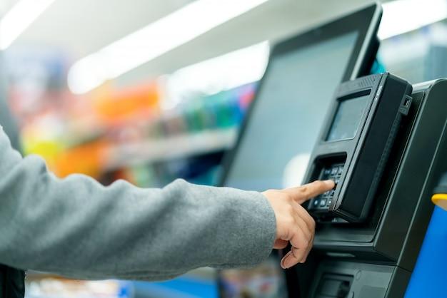 Macchina del cassiere del contatore di pagamento della mano del cliente del primo piano con il monitor nel deposito del supermercato Foto Premium
