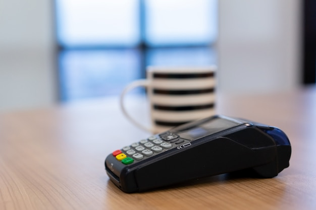 Macchina di pagamento con carta di credito al tavolo con una tazza di caffè bianco sul tavolo nella caffetteria Foto Premium