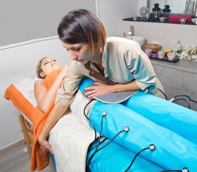 Macchina di pressoterapia gambe sulla donna nel centro di bellezza Foto Premium