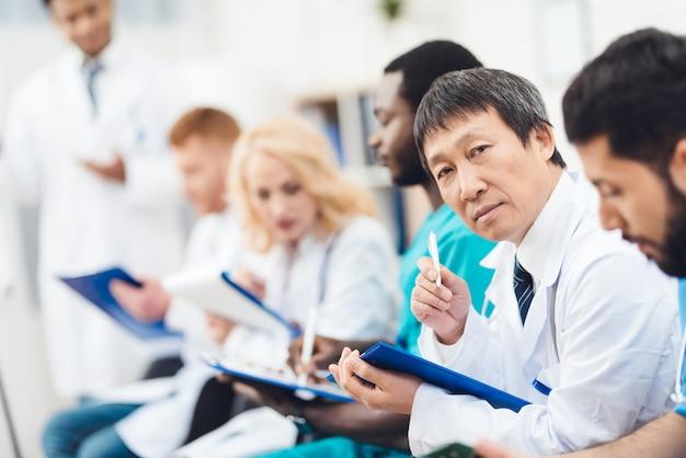 Macchina fotografica asiatica del dottore staring during the lecture. Foto Premium