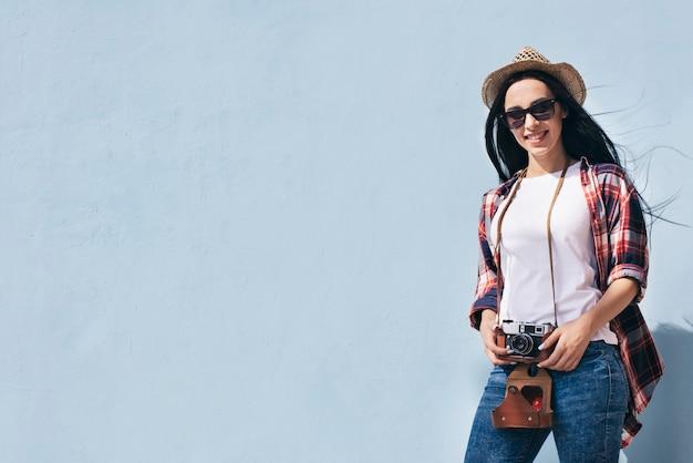 Macchina fotografica attraente sorridente della tenuta della donna che sta contro la parete blu Foto Gratuite