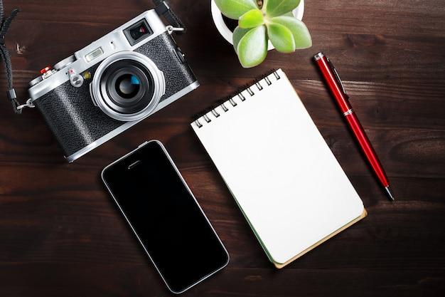 Macchina fotografica classica con la pagina in bianco del blocco note e penna rossa sulla tavola di legno di marrone scuro, tavola d'annata con il telefono e fiore verde Foto Premium