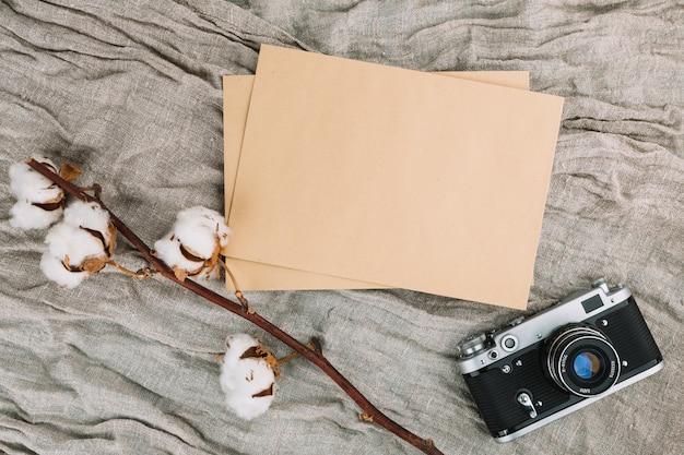 Macchina fotografica con carta bianca e ramo di cotone Foto Gratuite