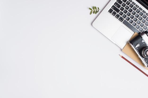 Macchina fotografica d'epoca; matita; aprire il computer portatile e ramoscello isolato su sfondo bianco Foto Gratuite