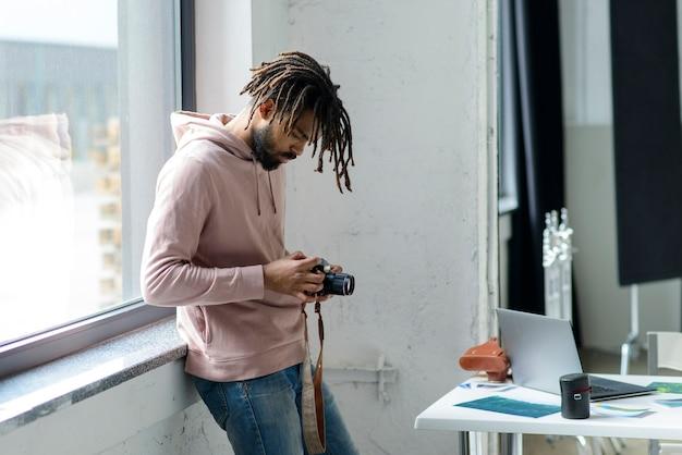 Macchina fotografica della tenuta dell'uomo del colpo medio Foto Gratuite