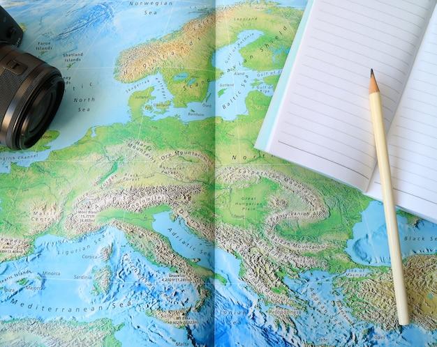 Macchina fotografica nera e taccuino foderato con matita bianca sulla mappa del mondo Foto Premium