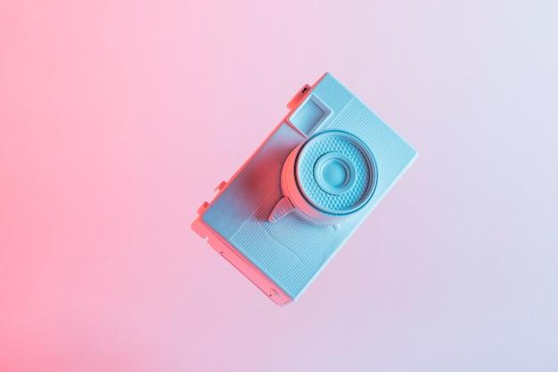 Macchina fotografica verniciata bianca contro fondo rosa Foto Gratuite