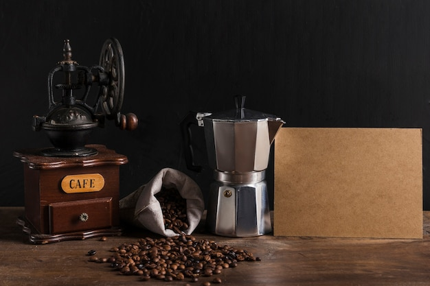 Macchine da caffè vicino a grani sparsi e cartone Foto Gratuite