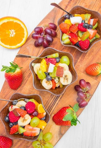 Macedonia di frutta con bacche fresche, arancia, cocco, mango e fette di banana Foto Premium