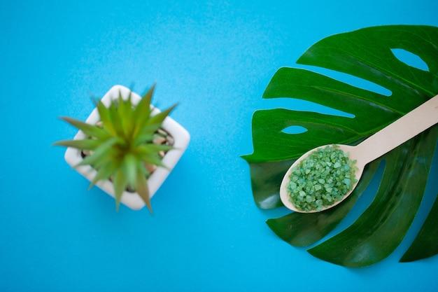 Macinazione del sale marino sul cucchiaio di legno della tabella misera blu-chiaro di legno Foto Premium