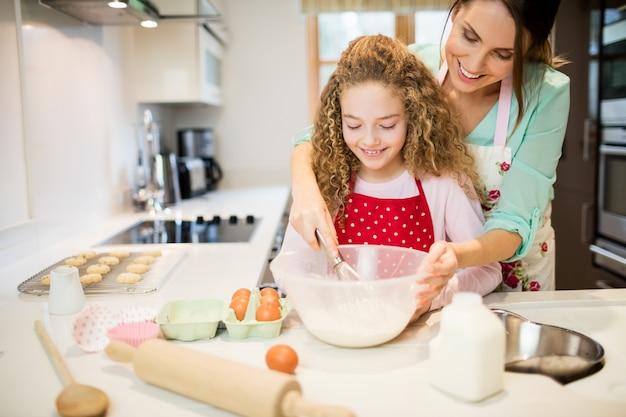 Madre aiutare la figlia a sbattere farina in cucina Foto Gratuite